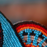 """Photo: Close up of a woman's headband, beaded by Saulteau First Nation artist Della Owens. Della told Amnesty International that, """"traditionally, when someone wasn't healthy and women got together to bead, we'd say a prayer with each bead we sewed."""" © Amnesty International"""