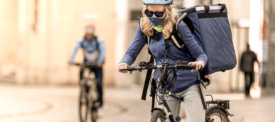 Photo of bike courier with long light coloured hair in urban centre wearing a face mask.