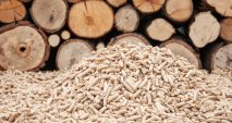 A pile of wood pellets is shown in front of a cross-section view of a stack of logs.
